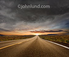 A long straight road, under dark storm clouds, leads to clearing skies and a bright sunrise in the distance in this stock photo about hope, possibilities, the way forward, and both success and better times ahead.
