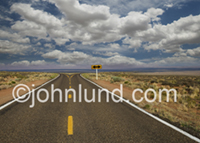 A long road leads across a desert landscape to a divergence, a fork in the road, a decision, a choice to be made.