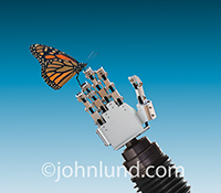 A Monarch butterfly alights on a Robot's hand in a stock photo contrasting nature and technology.