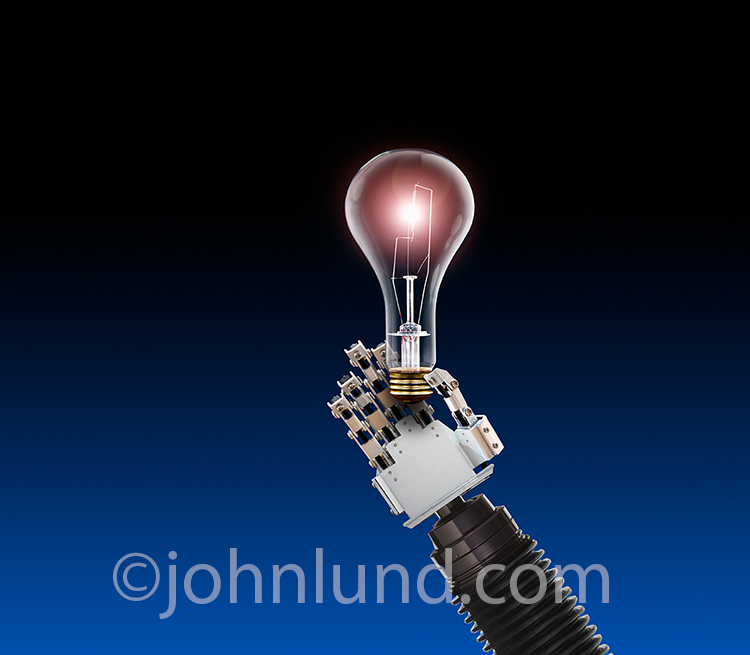 A robot hand holds up a glowing light bulb against a blue to black gradated background in a stock photo about artificial intelligence, creativity and ideas.