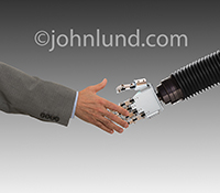 A businessman's had reaches out to shake a robot's hand in this stock photo about man's relationship to technology.