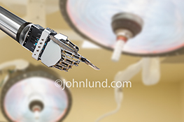 A robotic arm and hand holds a scalpel in an operating room in this stock photo about health, wellness and medical advances.