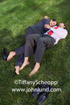 Latino or Mexican office personnel, a man and a woman, laying in the grass with their shoes off hugging each other. Office romance pics. Man laying on his back in the grass, woman on her side cuddled up to him.