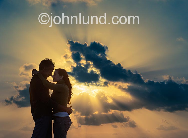 In an image about love and romance a couple embraces nose to nose against a brilliant God ray sunset sky.