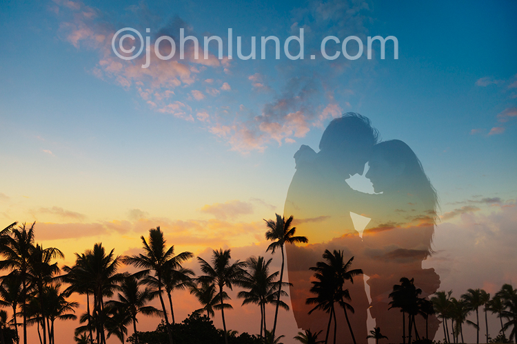 An embracing couple are silhouetted against a tropical sunset in an image of romance, togetherness and getting away from it all.
