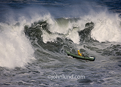 A man rows his small boat into a huge wave in this stock photo about courage, daring, and overcoming adversity.