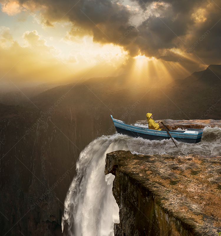 A man rows a boat over a waterfall in a stock photo about danger, risk and awareness.