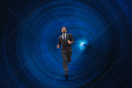 A businessman runs from technology through a futuristic tunnel of blue rings in a stock photo about overcoming adversity, fear, and the downside of technology.