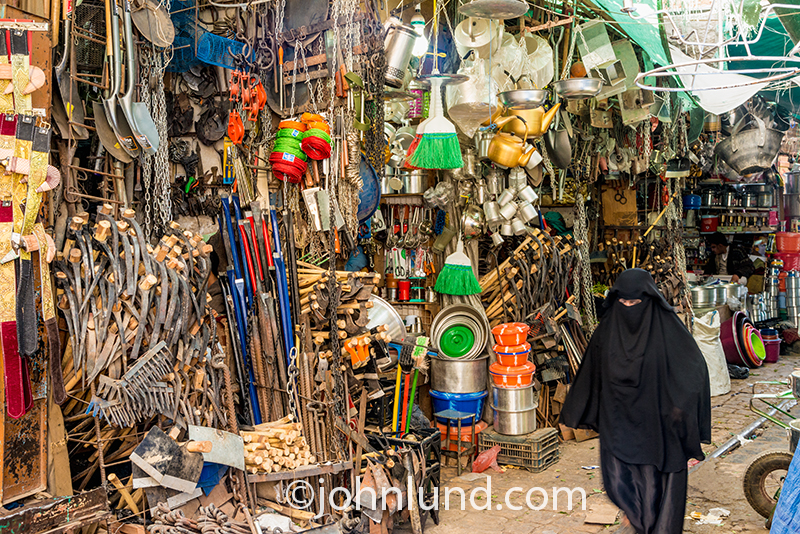An Abaya clad woman in the Old City of Saana, Yemen, walks through a narrow street filled with shops displaying their goods in a chaotic jumble of hardware.
