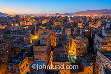 The capital city of Yemen, Saana, photographed at dusk as the street lights come on adding a warm glow to the cobblestone streets and ochre colored buildings with their ornate gypsum and fired brick geometric decorations.