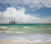 A tall sailing ship sails through blue tropical waters off of an idyllic beach in an image about getting away from it all, vacations, and adventure.