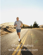 Photo of a man running down the center of a country road alongside the double yellow line.  The sun is at his back. The man is older, with gray hair and wearing shorts and a gray sweatshirt.