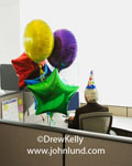 Funny foto of office employee working on his computer and wearing a funny party hat. Bright yellow, green, red, blue and purple party balloons are in the cubicle with him. A senior male employee having his own cubicle party. Ad pics for businesses.