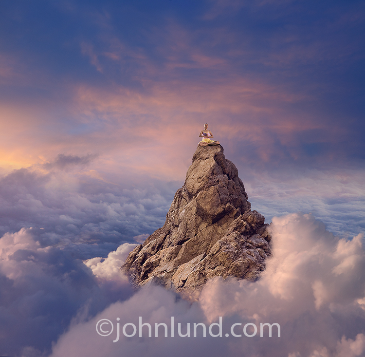 A senior woman meditates at the top of a mountain peak emerging from the clouds in a stock photo about spirituality, success and wonder.