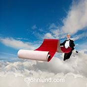 A butler rolls out a red carpet as he stands in the clouds in a stock photo depicting the concept of exceptional service and attention in the realm of cloud computing, online networking, and wireless communications.