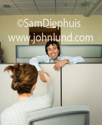 Picture of businesspeople shaking hands. A businesswoman is shaking hands with a businessman. The businessman is reaching over a cubicle wall or divider to shake hands with a woman. Business handshake stock photo.