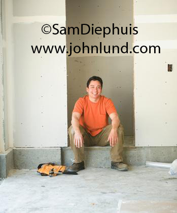 Picture of a sheet rock installer or carpenter sitting down on the floor at the days end. Man finished with his work installing sheet rock in a new building. Happy construction worker with his toolbelt at his feet.