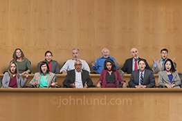 A jury sits in their jury box wearing expressions of shock and bewilderment at the testimony or evidence being presented in a humorous stock photo about presentations, decisions, and effective communications.