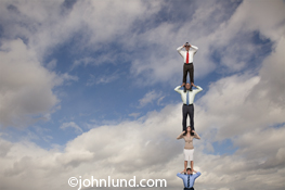 Four business people are standing on each other's shoulders to gain a high vantage point in an image about vision, searching the cloud, and the way forward. The person at the highest point is up in the clouds and looking through binoculars.