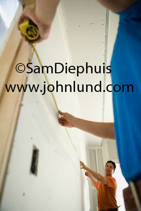 Two carpenters or contractors are measuring a wall with a tape measure. Picture of proffesional workmen doing their jobs. Ad pics.