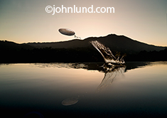 A skipping rock and its splash are frozen in mid air over a mountain lake in a concept photo about making a splash, possibilities, perseverance and taking action.