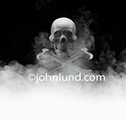 A skull and crossbones emerges from the mist in a stock photo about danger, risk and unnamed terrors.