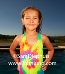 Adorable picture of a cute little girl wearing a swim suit and her hair is all wet because she has been swimming in the pool.  Brightly colored tie-dyed type suit. Waist up of smiling little girl in swim suit.
