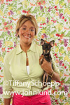 Woman Holding Pet Chihuahua.  The woman is wearing a lime green blouse and pink pants.  She is standing with her adorable little Chihuahua in front of floral print wallpaper. Chihuahua pics.