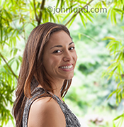 A smiling and happy woman is pictured against a natural outdoor background of brightly lit leaves.
