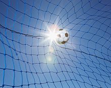 A soccer ball hits the back of the net in scoring a goal in a dramatic image about success, teamwork, and sports.