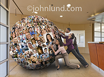 Three businesspeople struggle with a giant ball of portraits in an image about social media management in business. The environment is a high-end corporate lobby and the businessmen and women are ethnically diverse.