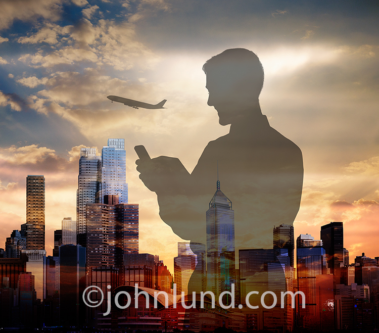 A businessman is silhouetted against an urban skyline and ascending jetliner as he uses his mobile device and social media to stay connected.