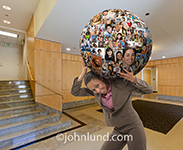 A businesswoman happily bears the weight of social media in this photo showing her with a globe of portraits on her shoulder.