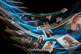 Social media flow is illustrated in this stock photo showing social media portraits flowing across the frame immersed in colored light trails representing networking, streaming media and the digital world.