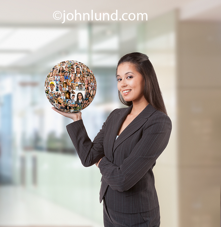 "Picture of a woman holding a sphere of people portraits in her hand in a metaphor for having social media ""In The Palm Of Her Hand"". In other words, having a handle on social media."