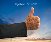 A woman executive's thumb is held up in front of a sunrise while her hand is multiple-exposed with a series of people's faces to create a positive image of social media and social networking.