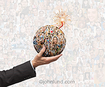 A hand holds a bomb shaped orb of social media portraits, complete with burning fuse, in a stock photo about social networking disruption and change.