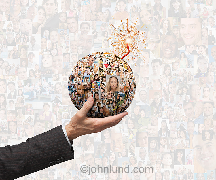 A hand  holds a spherical bomb, with a burning fuse, created from social media photos, and against a backdrop of over a hundred model-released, greyed-out social networking portraits, in a stock photo about the explosive power of social media.