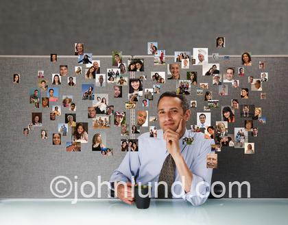 Photo of a businessman at his desk in his cubicle surrounded by small pictures of the people in his social and business network.