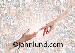 Two hands reach out to each other in a burst of light with a background of hundred of individual people portraits in an image about online connections through social media and networking.