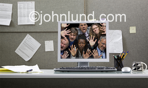 A crowd of angry people look out of a computer in an office setting indicating the downside of social networking.