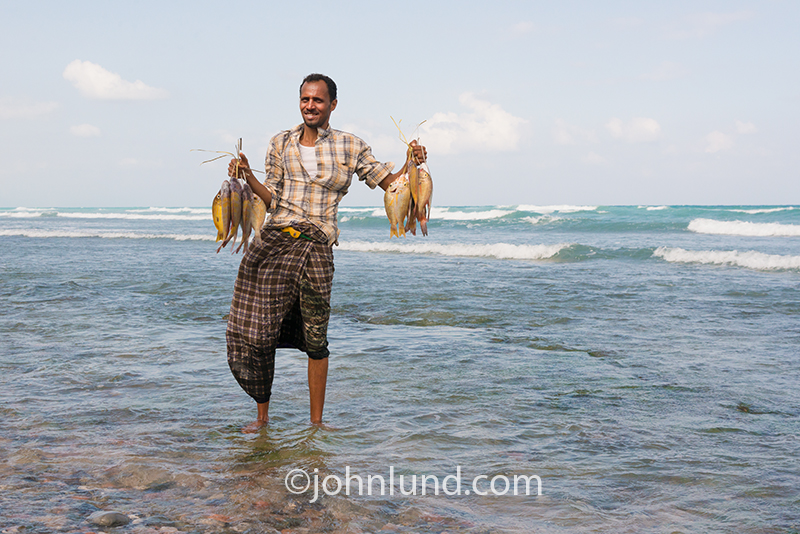 A fisherman stands in the surf holding his catch on the island of Socotra off the coast of Yemen.
