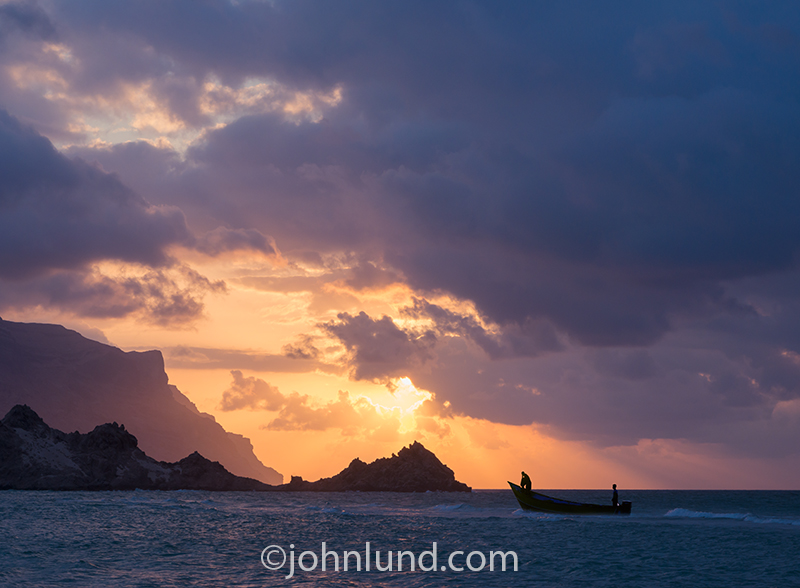 A Socotran fishing boat returns at sunset from the day's fishing. The boat is silhouetted against the rays of the setting sun and rock outcroppings beyond the white sand beaches.