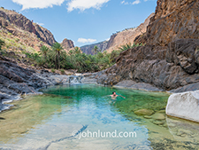 An idyllic oasis-like swimming hole compete with palm tress offers a cool refreshing respite from a long arduous hike on Socotra island in the Indian ocean.