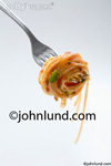 Picture of spaghetti wrapped around tines of a fork in a stock food photo. Delicious looking spaghetti noodles neatly twirled onto the end of a fork ready for you to take a bite.