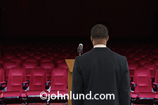 Photograph of an African American man, from behind, as he stands at a podium and microphone in front of an empty theater in a concept photo about issues surrounding marketing, advertising, demographics and attracting clients.