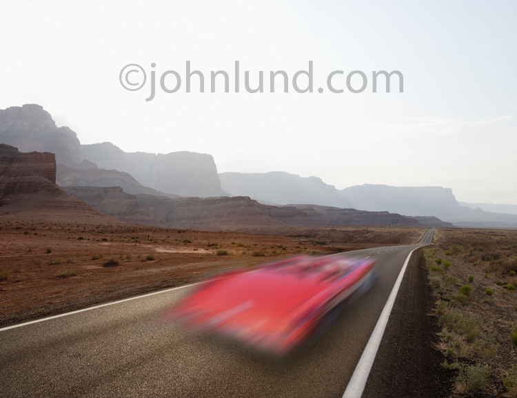 A fast car is a red blur on a lonely Southwestern road in an image about speed, freedom and the way forward.
