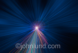 Speed in communications technology is illustrated in this stock photo of zooming brightly colored light trails in a predominantly business-blue background.