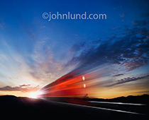 A bright red locomotive speeds forward out of a sunrise or sunset in a photo illustrating the concepts of speed and power.