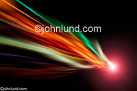 A comet-like burst of light streaks through the frame of this concept stock photo. Wild streaking lights of many colors with a bright fire ball at the head.